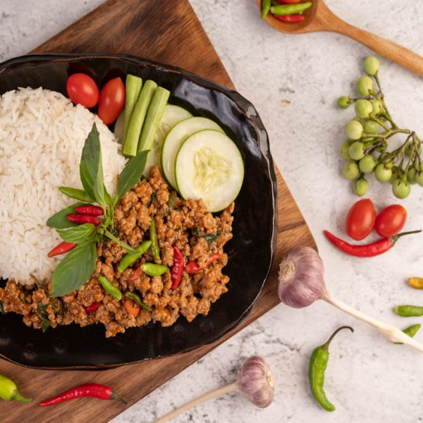 image of Spicy minced pork salad with rice, chilies, and tomatoes in a black plate.